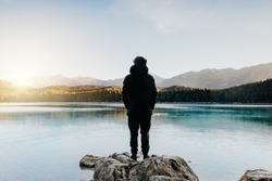 Person from behind looks at beautiful lake at sunrise. Relaxed, peaceful, thoughtful, happy and free at the mountain lake.
