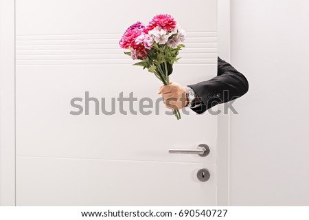 Person giving a flower bouquet from behind a door