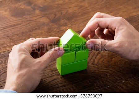 Person Hand Building House Of Blocks On Wooden Desk. Real Estate Concept #576753097