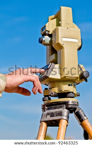 person hand making data input into survey equipment tool theodolite