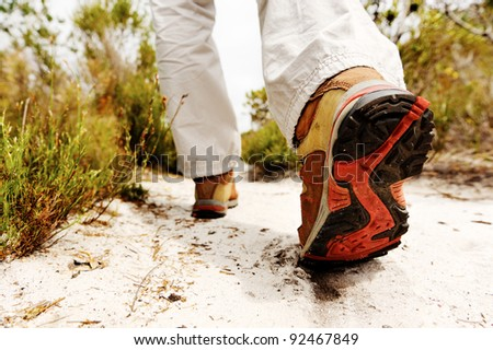 person hiking outdoors, boot on sandy pathway in the wilderness. trekking