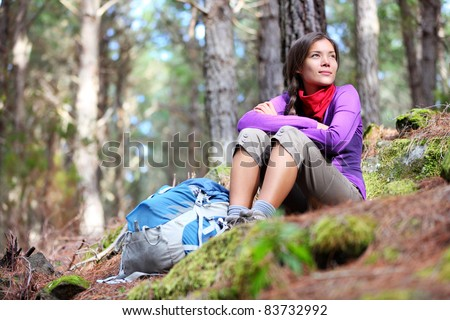 Person hiking - woman hiker sitting in forest resting during hike in beautiful forest. Orotava vally, Aguamansa, Tenerife, Canary Islands.