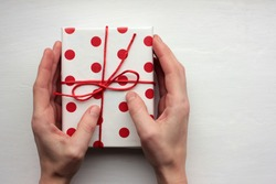 Person holding a gift box. Overhead view of female hands with present wrapped in red and white polka dot pattern paper on white background. Top view, copy space, selective focus