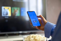 Person holding a smartphone connected to a VPN while watching shows on a streaming service on Television.
