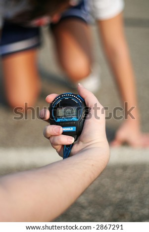 person holding a stop watch in front of a runner ready to start a race