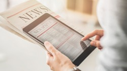 Person holding and reading news from tablet