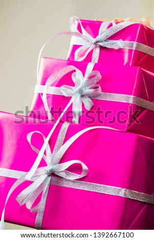 Person holding big stack of presents, pink gift boxes with white ribbons.