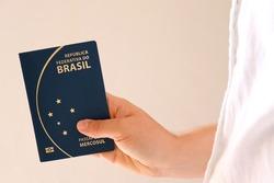 Person holding Brazilian Passport. Travel concept. | Translation: Federative Republic of Brazil. Mercosur passport.