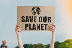 Person holding brown save our planet cardboard poster. Save the planet on a paper banner in men's hand. Human holds a cardboard with an inscription: Save our planet