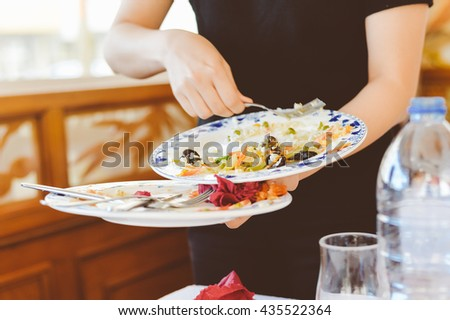 Person holding collecting in hands dirty dishes restaurant background ストックフォト ©