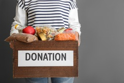Person holding donation box with food on gray background, closeup