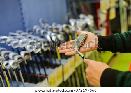 Person holding in hand club at a golf shop. Closeup photo of choice concept