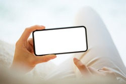 Person holding in hands mobile phone horizontally with empty white screen, mockup photo of smartphone for your own design