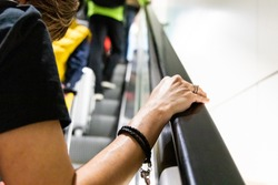 Person holding onto handrail of escalator in public risks  infected with germs, bacteria, virus.