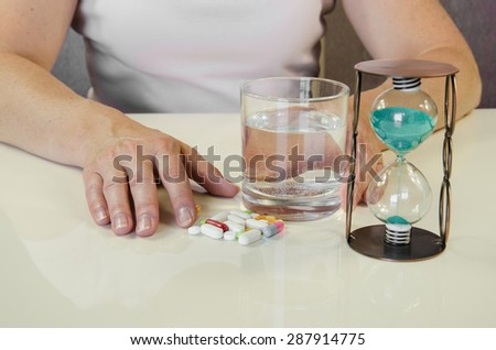 person holding pill,clock and glass of water