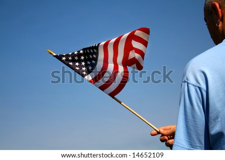 Person holding the American flag outside with a beautiful blue sky as the background.