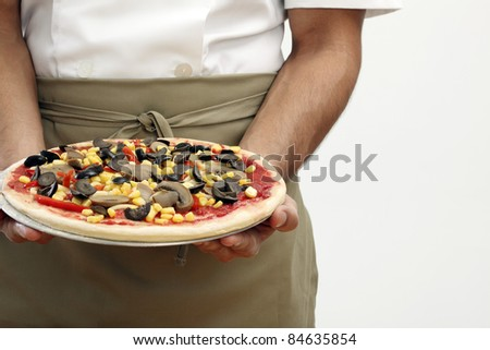 Person holding the uncooked pizza
