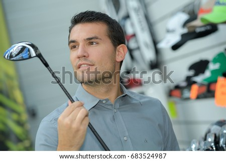 person holding with hand golf club in a golf shop