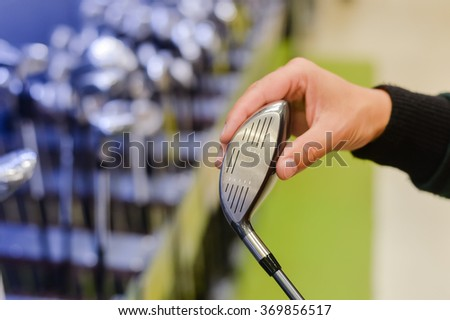 Person holding with hand golf club in a Golf Shop. Closeup photo