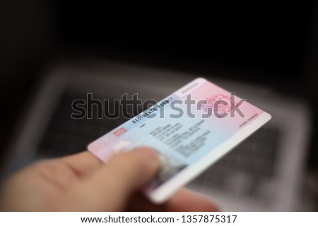 Person holds UK Residence Permit - BRP card in hand and computer in the background. Immigration concept image.