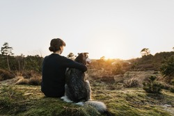 Person hugging a dog outdoors in beautiful nature. They enjoy the sunset. Emotional connection with trust. Happy content time together. Friendship between humans and dogs. Hugs.