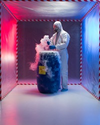 person in a protective suit and gas mask working with steaming substances over a blue waste drum marked as bio hazardous inside a containment tent