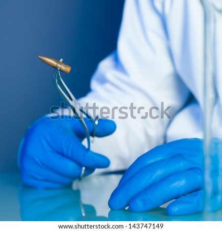 person in a white lab coat and blue rubber gloves, holding a bullet on a reflective surface