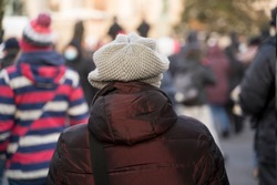 Person in a winter coat walking alone in a crowd, image taken from the back