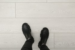 Person in black boots standing on wooden floor, top view. Space for text