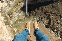 Person in blue jeans and beige sneakers sits swinging legs on high cliff edge near narrow waterfall on sunny day close view from above.