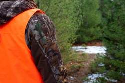 person in camouflage wearing a hunter orange vest to be visible in the woods to hunters