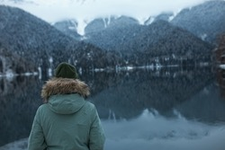 Person in green hat and parka looking in distance from riverbank, facing calm, beautiful mountain lake, surrounded with enormous hills covered with coniferous trees, snowy peaks showing up on horizon
