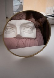 person in pink dressholding a white  eye statue. Reflection in the mirror