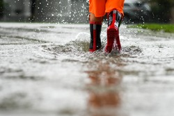 Person in rainboots walking through water