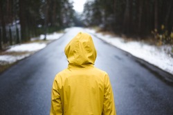 Person in the yellow raincoat is standing on the road in the middle of the forest.
