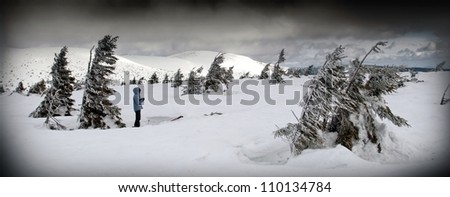 Person in Windy Winter Landscape (panorama with dark framing)