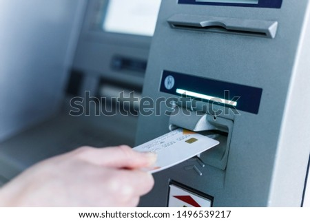 Person insert card to automated teller machine. Cashing non-cash money by individual. #1496539217