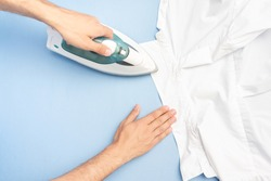 Person ironing his shirt, men's hands with iron, closeup, top view, close up