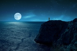 Person is standing in the edge of a cliff against the sea and full moon, under stars and moon light.