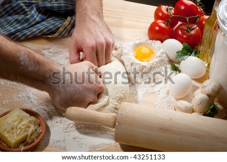 Person kneading dough on wooden table top with a lot of flour