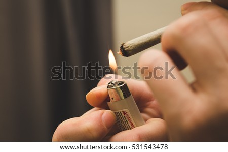 Person lighting a joint, spliff, or cigarette