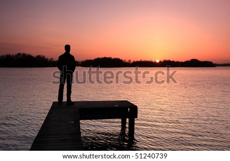 Person looking at spring sunset over a Dutch lake.