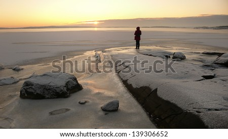 Person looking at sunset in a winter landscape by the sea