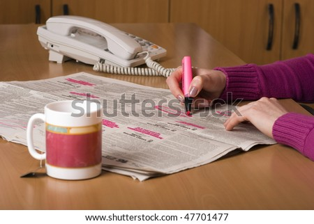 Person looking for work in the newspaper. Person is holding a bright pink highlighter pen and circling interesting jobs whilst drinking a cup of coffee.