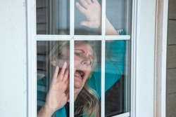 person looks out their front door with an anxious expression wanting freedom