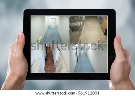Person Monitoring Cameras Live View Of Home On The Digital Tablet