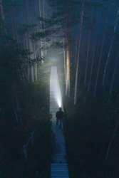 Person on trail with headlamp at night in misty forest