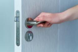 Person opens the door. Hand on door handle