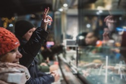 Person ordering a fresh kebab or gyros in a fast food stall or vendor outside in a city. Visible hands showing V sign to order food over the counter in festive evening.
