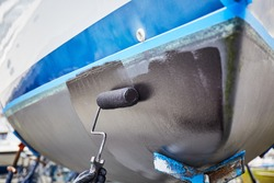 Person painting a boat's bottom with a fresh paint, using roller and black paint, outdoors in the boatyard